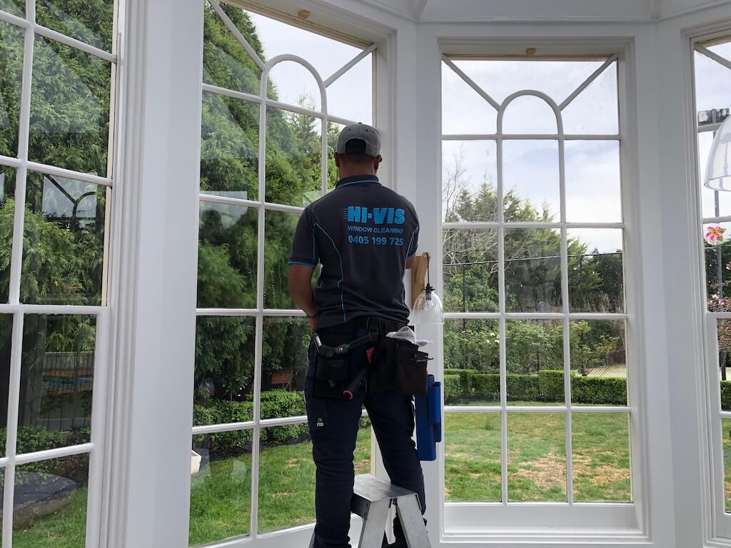 Hi Vis Team Member Cleaning Dirty Windows